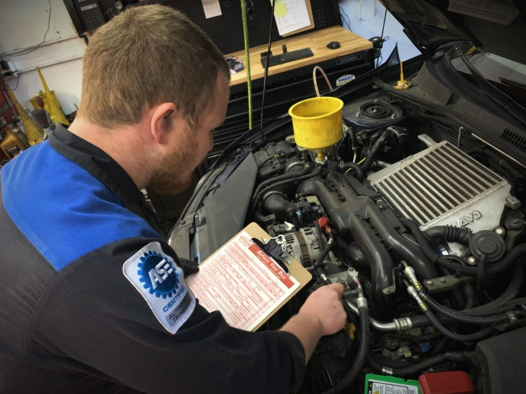 Technician inspecting a car before buying a used Subaru.